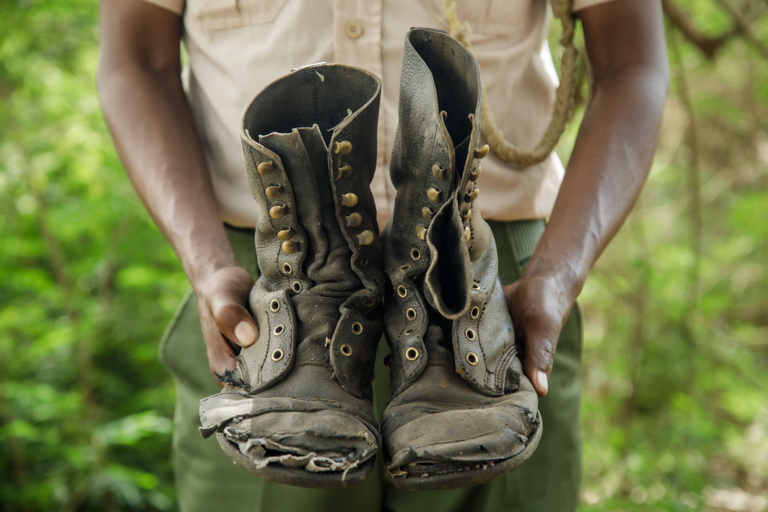 A Ranger stands, only hands and torso visible, with a pair of old, worn and torn boots.